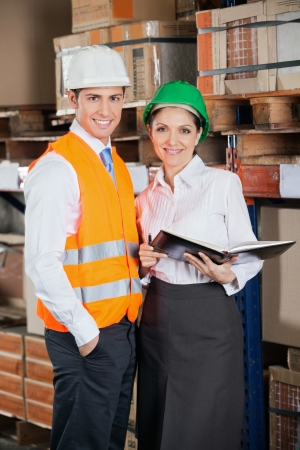 Portrait of two young supervisors with book standing at warehouse Stock Photo - 16191686
