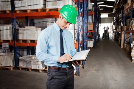 Young male supervisor writing notes at warehouse photo