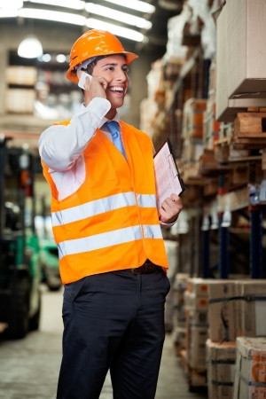 warehouse worker: Portrait of young male supervisor using cell phone at warehouse