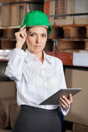 Portrait of confident young female supervisor with digital tablet standing at warehouse photo