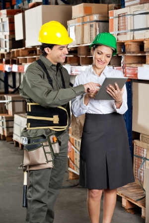 Young female supervisor and foreman using digital tablet at warehouse photo