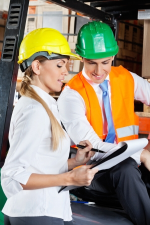Female supervisor communicating with colleague sitting in forklift at warehouse photo