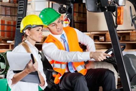 Male supervisor in forklift showing something to colleague with clipboard at warehouse photo
