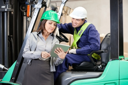 Female Supervisor And Forklift Driver Using Digital Tablet photo