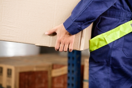 Foreman Carrying Cardboard Box At Warehouse photo