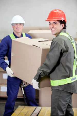 safety box: Foremen Lifting Cardboard Box in Warehouse