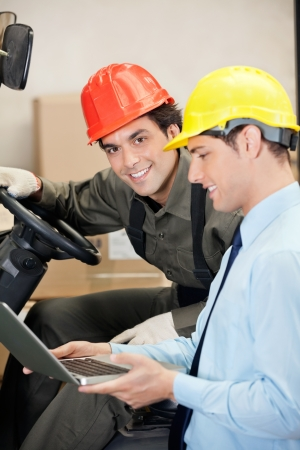 Forklift Driver With Supervisor Using Laptop photo