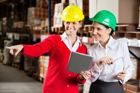 Female Supervisor With Colleague At Warehouse photo