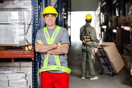 Mid Adult Foreman With Arms Crossed At Warehouse photo