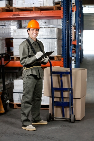 sack truck: Male Supervisor Writing On Clipboard Stock Photo