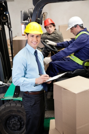 forklift truck: Supervisor With Foremen Working At Warehouse Stock Photo