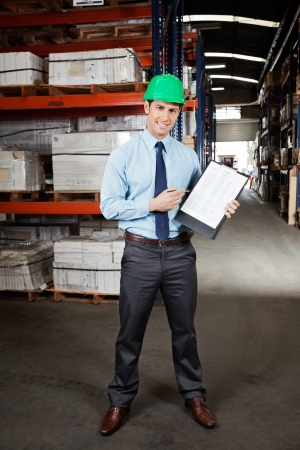 Confident Supervisor Displaying Clipboard photo