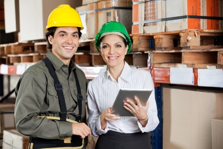 instructing: Supervisor Instructing Foreman At Warehouse Stock Photo