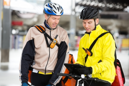 delivery man: Courier Delivery Men With Bicycles Using Digital Tablet