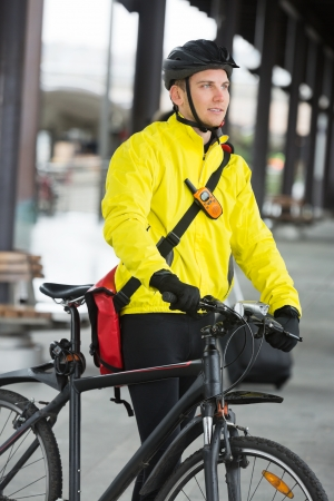 Young Man With Bicycle And Bag Looking Away photo