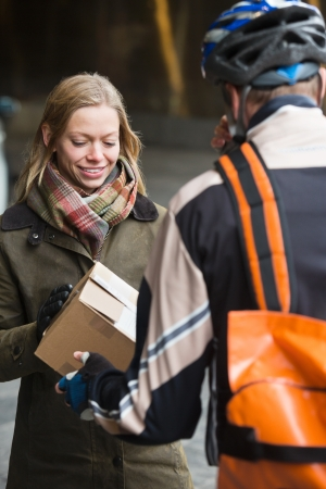 Young Woman Receiving A Package From Courier Delivery Man photo