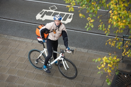 Young Male Cyclist With Backpack On Sidewalk photo