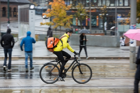 messenger: Male Cyclist With Backpack On Street Stock Photo