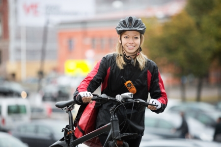 Female Cyclist With Courier Bag On Street photo