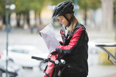 Female Cyclist Putting Package In Courier Bag photo