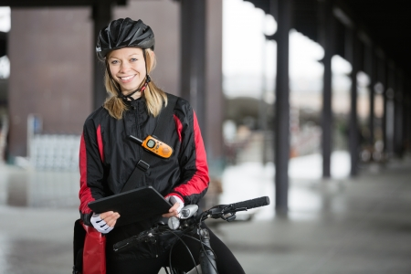 two way: Female Cyclist With Courier Bag Using Digital Tablet