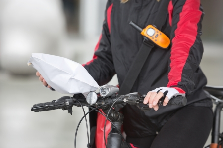 Female Cyclist Holding Courier Package photo
