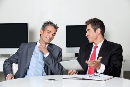 Businessman Holding Digital Tablet Sitting With Colleague At Des photo