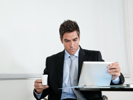 Businessman With Coffee Cup Using Digital Tablet Stock Photo - 16470506