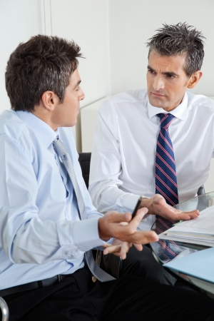 Young Businessman And Colleague Discussing Paperwork Stock Photo - 16470514