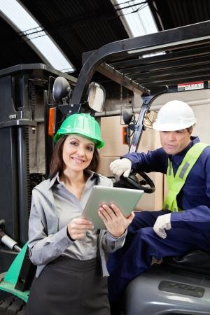 fork lift: Female Supervisor And Forklift Driver With Digital Tablet
