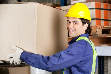 Young Foreman Lifting Cardboard Box photo