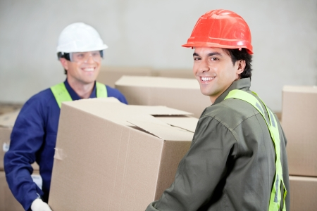 Foremen Lifting Cardboard Box At Warehouse photo
