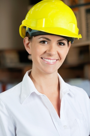 Female Supervisor Wearing Hardhat At Warehouse photo