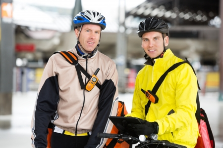 Courier Delivery Men With Bicycles Using Digital Tablet photo