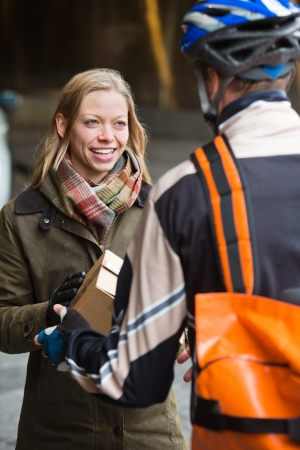 Smiling Young Woman Receiving A Package From Courier Delivery Ma photo