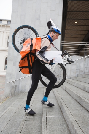 Courier Delivery Man With Bicycle And Backpack Walking Up Stairs photo