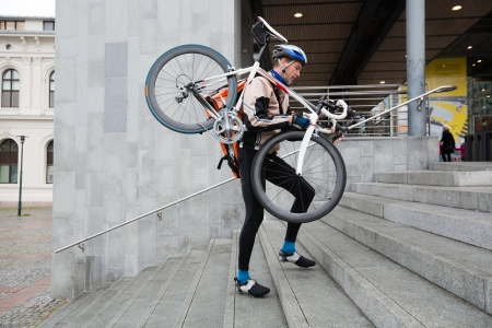 Male Cyclist With Bicycle On His Shoulder Walking Up Steps photo