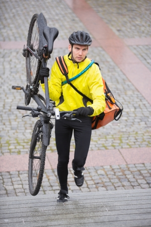 Male Cyclist With Bicycle And Courier Bag Walking Up Steps photo