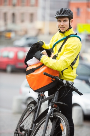 Male Cyclist Putting Package In Courier Bag On Street photo