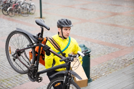 Courier Delivery Man With Package And Bicycle Walking Up Steps photo