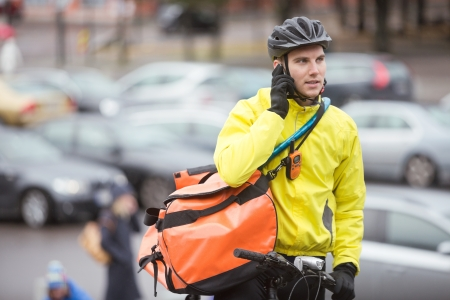 Male Cyclist With Courier Bag Using Mobile Phone On Street Stock Photo - 16470596