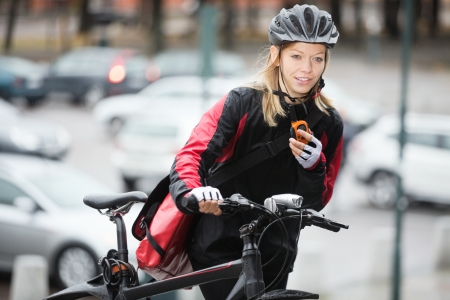 Female Cyclist With Courier Bag Using Walkie-Talkie photo