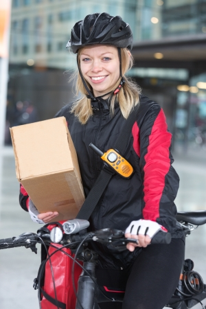 Female Cyclist With Cardboard Box And Courier Bag On Street photo