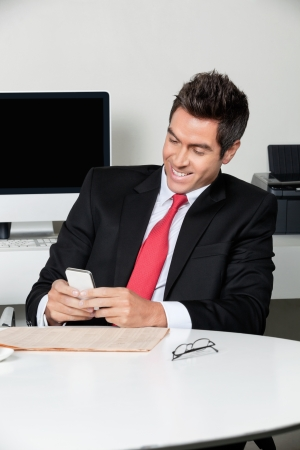 Businessman Using Cell Phone At Desk Stock Photo - 16487182