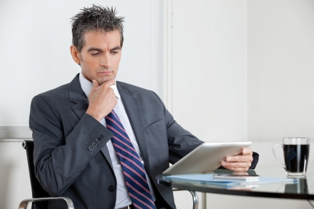 Contemplative Businessman Using Digital Tablet In Office Stock Photo - 16487155