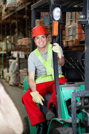 Foreman Sitting In Forklift At Warehouse photo