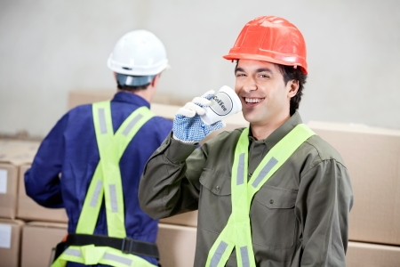 Foreman Drinking Coffee While Colleague Working At Warehouse photo
