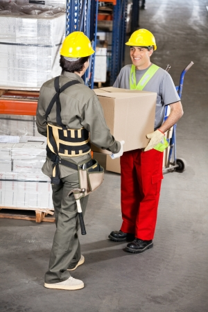 Foremen Carrying Cardboard Box At Warehouse photo