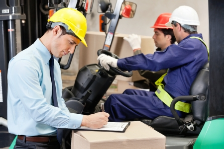 Male Supervisor Writing On Clipboard At Warehouse photo