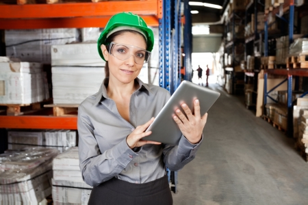 workplace safety: Female Supervisor Using Digital Tablet At Warehouse Stock Photo